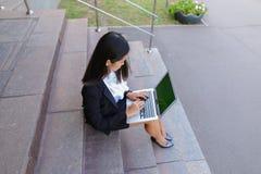 Asiatische schöne junge Frau hält im Handlaptop und im Lächeln, L lizenzfreie stockfotos
