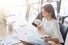 Asiatische schöne junge Geschäftsfrau weißes Hemd im trinkenden Lattekunst-Herzkaffee, der an Schreibtisch arbeitet Lizenzfreies Stockfoto