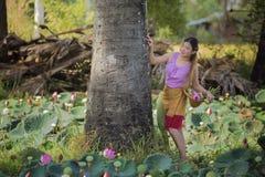 Asiatische Schönheit, die auf dem Lotosgebiet geht lizenzfreies stockfoto