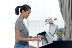 Asiatische Schönheit, die zu Hause Digitalpiano spielt Gesehen von der Seitenansicht während sie Klaviertasten durch beide Hände  lizenzfreie stockbilder