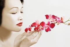 Asiatische Schönheit mit Orchideen stockfotos