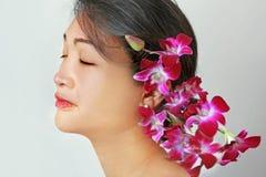 Asiatische Schönheit mit Orchideen Stockbild