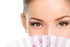 Asiatische Schönheit mustert - die Make-upfrau, die mit Fan schaut Stockfotografie