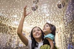 Asiatische Schwester- und Kinderfreude in der hellen Dekoration an der Nachtpartei schöne Zeit zu cerebrate Konzept lizenzfreies stockbild