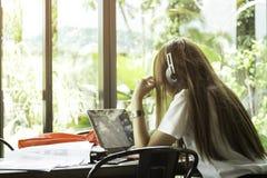 Asiatische Studenten in der Uniform mit Kopfhörer studierend in der Kaffeestube lizenzfreie stockfotos