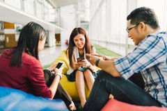 Asiatische Studenten oder Mitarbeiter, die zusammen Smartphones verwenden Moderner Lebensstil des Spaßes, Soziales Netz Stockfotografie