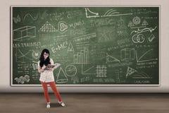 Asiatische Studentinlesung auf schriftlichem Brett in der Klasse Stockbild