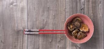 Asiatische Tabelle mit Essstäbchen und getrockneten Shiitakepilzen in einer Schüssel Stockbild
