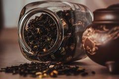Asiatische Teekanne auf Stand und Glas mit dem Zerstreuen des Tees Stockfotos