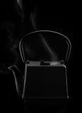 Asiatische Teekanne des schwarzen Eisens mit Dampf stockbilder