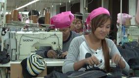 Asiatische Textilindustrie-Fabrik: Weibliche Arbeitskräfte Mitgliedstaates Kleideran nähenden Tischen stock video