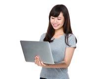 Asiatische Uhr der jungen Frau auf der Laptop-Computer Stockfoto