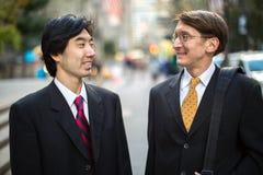 Asiatische und kaukasische Geschäftsmannunterhaltung Stockfotografie