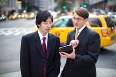 Asiatische und kaukasische Geschäftsmannunterhaltung Stockfotos