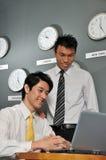 Asiatische Unternehmensleiter im Raum voll der Borduhren Stockfotos