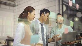 Asiatische Unternehmensleute, die Geschäft im Büro besprechend sich treffen