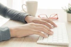 Asiatische weibliche Hände benutzen eine Computertastatur lizenzfreie stockfotografie