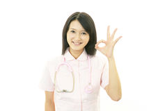 Asiatische weibliche Krankenschwester mit okayhandzeichen Stockbild