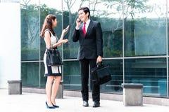 Asiatische Wirtschaftler, die draußen mit Handys sprechen stockbilder
