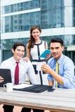 Asiatische Wirtschaftler, die draußen mit Kaffee arbeiten Lizenzfreies Stockfoto
