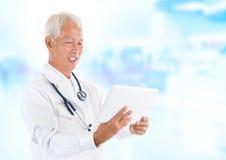 Asiatischer älterer Doktor, der TablettepC verwendet Stockbild
