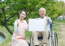 Asiatischer älterer Mann, der auf einem Rollstuhl mit Pflegekraft und weißem Brett sitzt Stockbilder