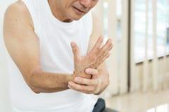 Asiatischer älterer Mann, der die Handgelenkschmerz oder -verletzung hat Stockbilder