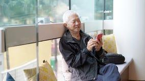 Asiatischer älterer Mann, der intelligentes Telefon verwendet Stehen Sie durch technolo in Verbindung stockbilder
