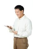 Asiatischer älterer Mann, der Tablette verwendet Stockbild