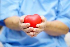 Asiatischer älterer oder älterer Frauenpatient alter Dame, der rotes Herz in ihrer Hand auf Bett in Pflegekrankenstation hält lizenzfreie stockfotografie