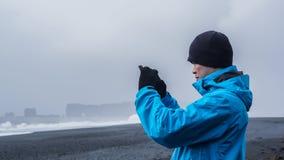 Asiatischer advanture Mann am Island-Schwarzstrand, der Foto macht Lizenzfreie Stockbilder