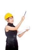 Asiatischer Architektenmädchen-Abnutzung Hardhat und zeigen einen Stift oben Lizenzfreies Stockfoto