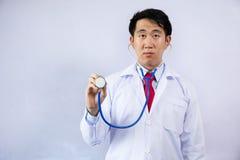 Asiatischer Arzt, der Stethoskop hält und über hellblauem Hintergrund überprüft lizenzfreies stockfoto