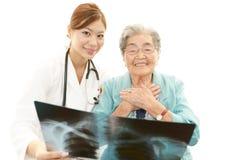 Asiatischer Arzt und ältere Frau Stockfotografie