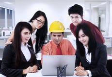 Asiatischer Auftragnehmer, der Team im Büro erklärt Lizenzfreies Stockfoto