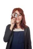 Asiatischer Büromädchenblick durch Lupe und Lächeln Stockbild