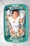 Asiatischer Baby-Schlaf auf Korb Stockbilder