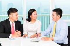 Asiatischer Banker, der Versicherung an Paare verkauft Stockfotografie