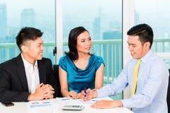 Asiatischer Banker, der Versicherung an Paare verkauft Lizenzfreie Stockfotografie
