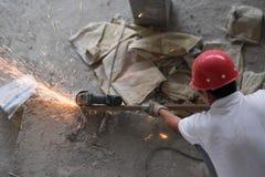 Asiatischer Bauarbeiter Cutting Metal Sparks Stockfotos