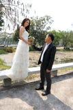 Asiatischer Bräutigam, der seiner Braut einen reizenden Blumenstrauß gibt Stockfoto