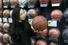 Asiatischer Chinese, der Bälle, Fußball ballsarea im Zehnkampfspeicher wählt Lizenzfreie Stockfotos
