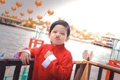 Asiatischer chinesischer Junge in der traditionellen Ausstattung des Chinesischen Neujahrsfests neues Mondjahr feiernd lizenzfreie stockbilder