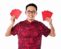 Asiatischer chinesischer Mann, der rotes Paket anhält Stockfotografie