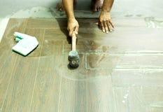 Asiatischer Dachdeckererbauer, der Bodenfliese installiert Stockbilder