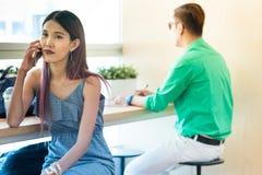 Asiatischer Damengebrauch und -gespräch im intelligenten Handy beim Sitzen in c lizenzfreies stockfoto