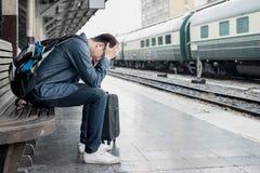 Asiatischer deprimierter Reisender, der an der Bahnstation nach Fehlern wartet Stockfotografie