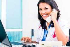 Asiatischer Doktor in der Büroverwaltungsarbeit lizenzfreie stockbilder