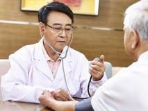 Asiatischer Doktor, der Blutdruck eines älteren Patienten überprüft Stockfotos