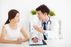 Asiatischer Doktor, der mit weiblichem Patienten spricht Stockbild